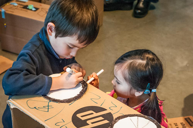 Children coloring on cardboard