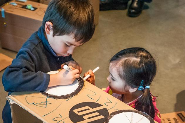 Children coloring on cardboard