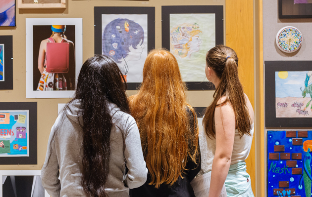 image of students looking at art in the Community Corridor