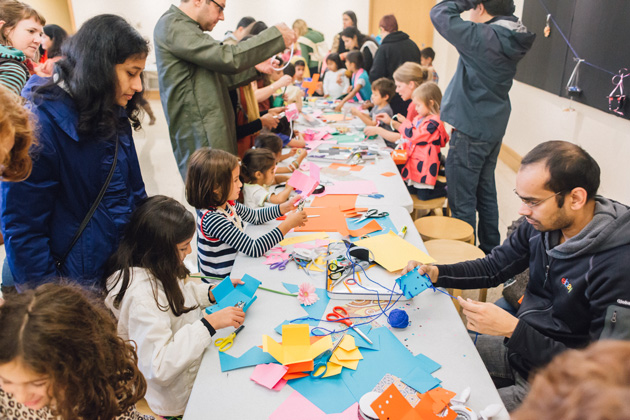 Children and adults making art with paper
