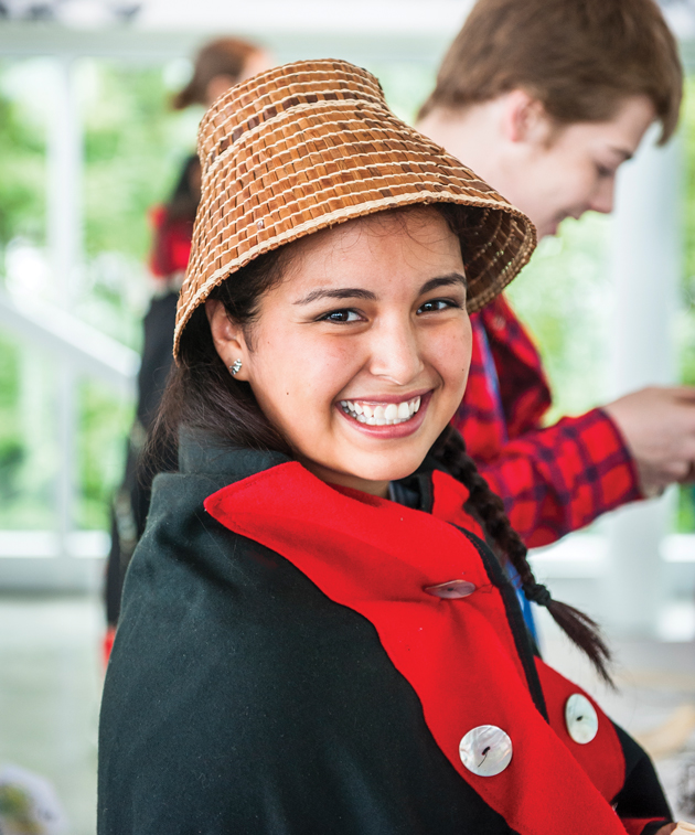 A woman wearing a woven hat and button blanket smiling at the camera