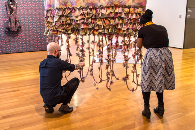 Two people looking at a textile-based art installation