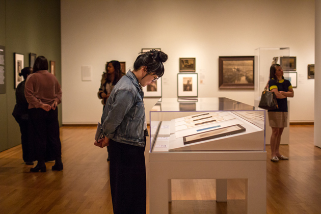 Photo of a woman looking at a display case of art from the exhibition Double Exposure