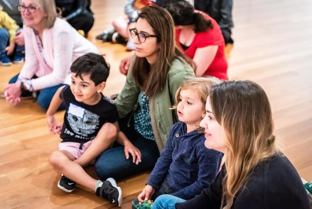 group of children and teachers sitting in a gallery and listening
