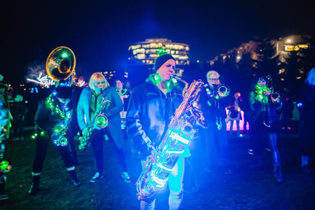 Musicians with instruments wrapped in decorative lights performing in the park
